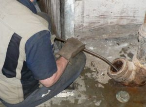 a plumber snaking a drain pipe