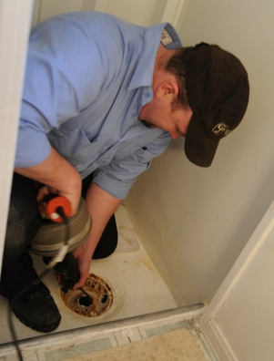plumber unclogging a shower drain